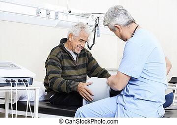 fysiotherapeut, het onderzoeken, senior, patiënt, op bed