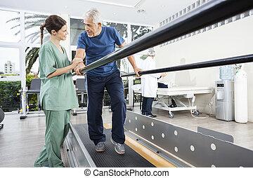 fysiotherapeut, kijken naar, senior, patiënt, wandelende, tussen, parall