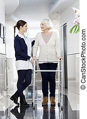 fysiotherapeut, kijkende vrouw, terwijl, walker, gebruik, ...