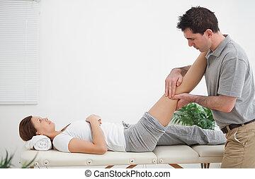 fysiotherapeut, masserende handen, een, been, terwijl, plaatsing, informatietechnologie, op, zijn, schouder, in een kamer