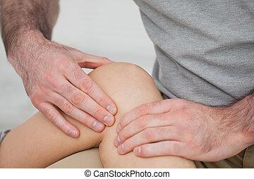 fysiotherapeut, masserende handen, pijnlijk, knie