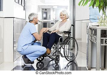 fysiotherapeut, vasthouden, het glimlachen, senior, vrouwenhand, op, wheelchai