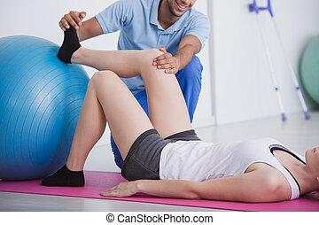 fysiotherapeut, vasthouden, knie, en, voet, van, zijn, patiënt, gedurende, rehabilitatie, met, een, bal