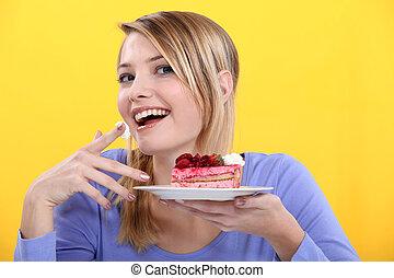 gâteau, femme mange, jeune, morceau