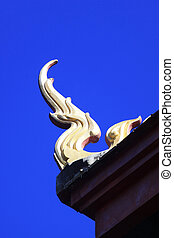 Gable apex of Thai temple with blue sky background.