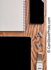 Gadgets and notebook on wood.