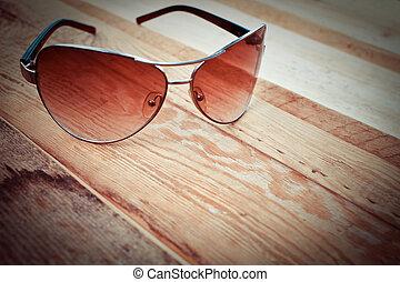 gafas de sol, en, un, de madera, plano de fondo