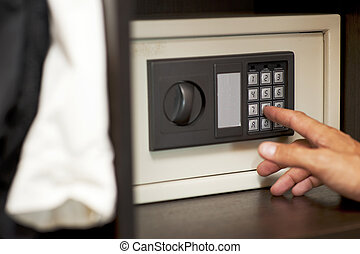 gaining code to the locked safe - Male hand gaining an...