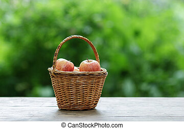 gala apples in a wicker basket, on wooden table
