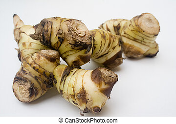 Galangal root - A stack of galangal root isolated against a ...
