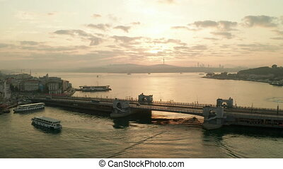 Galata Bridge over Bosphorus in Golden Sunrise light with Boats on Water, Aerial Establishing Shot slide left