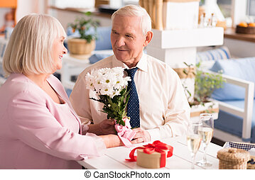 Gallant grey haired man presenting his lady flowers