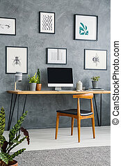 Gallery of posters above desk with computer desktop in grey home office interior with chair. Real photo