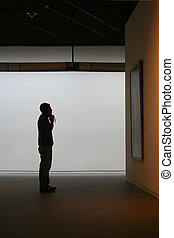 gallery - a person looks at a painting in a gallery