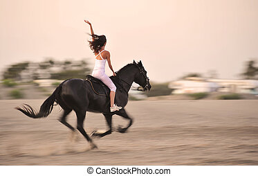 galloping black stallion with a young girl on a beach