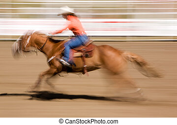 A horse galloping fast with a female rider - motion blur.