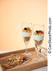 Galsses with low calorie dessert with granola, greek yogurt and fresh berries on wooden tray