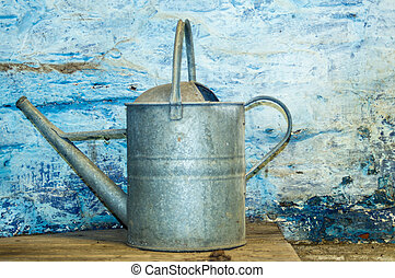 Galvanised - Watering can against a washed blue wall