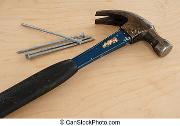 Galvanized Nails and a Claw Hammer on a Wooden Board