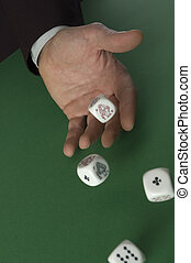 hand throwing dices on green background close up