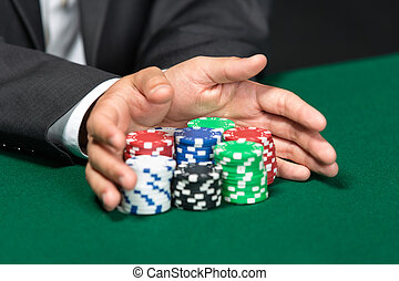 """Poker player going """"all in"""" pushing his chips forward. Symbol of addiction to the poker"""