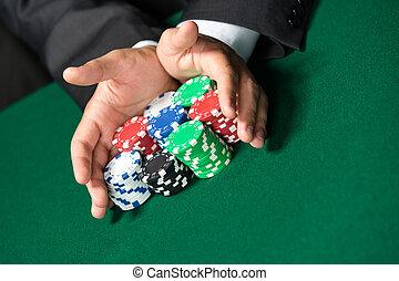 "Gambler stakes ""all in"" pushing his poker chips forward. Risky entertainment of gambling"