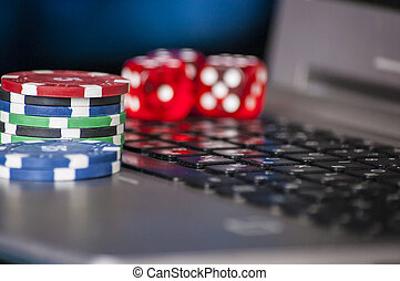 Gambling chips and red dice on laptop keyboard background