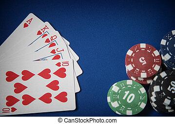 Gambling chips and royal flush poker hand on blue felt background