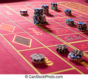 Gambling chips on red roulette table