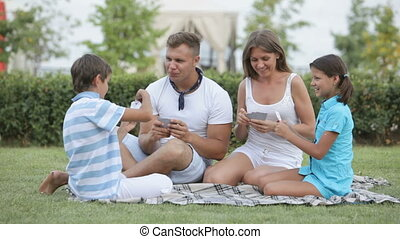 Gambling family - Parents and kids sitting on the grass and...