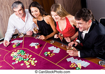 Gambling - Portrait of people sitting at the table and...