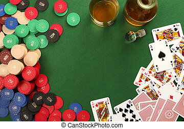 Photo of a poker table with gambling chips, cards and whisky.