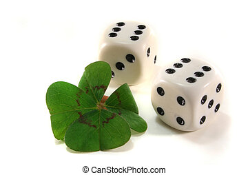 Gambling - two cubes with four-leaf clover leaf on white...
