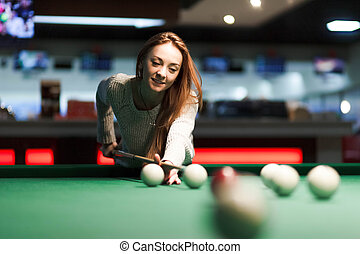 Gambling woman plays snooker in a billiards club