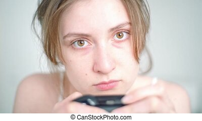 Game addiction. A female gamer's face with a game dependency close-up when she plays a console jostik in front of the TV 4k