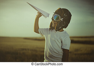 Game, Boy playing to be a classic pilot, wearing a fur hat, glasses and wings made of cardboard as a toy