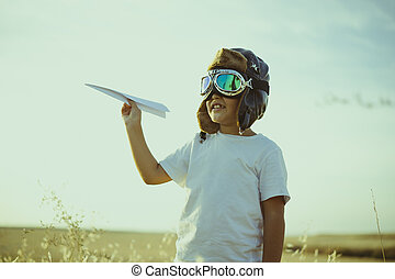 Game, Boy playing to be airplane pilot, funny guy with aviator cap and glasses, carries in his hand a plane made of paper