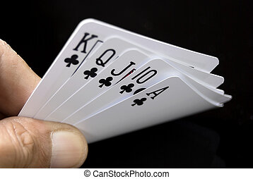 Royal Flush held by hand against black background