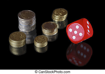 Piles of money and a red dice