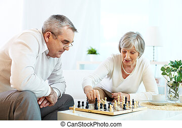 Game of chess - Portrait of senior couple playing chess at...