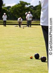Game of Lawn Bowls - Men playing lawn bowls. Very narrow ...