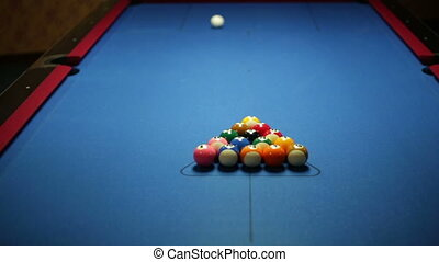 Game of pool with blue felt pool table, shot of break