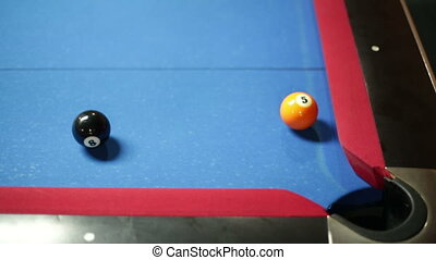 Game of pool with blue felt pool table, sinking black in corner pocket