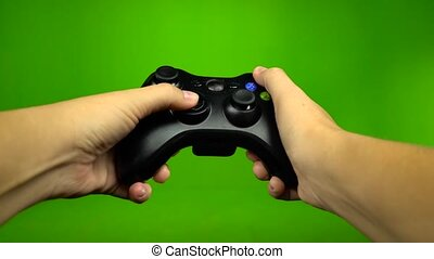 Game player hands controlling joystick keys playing on green...