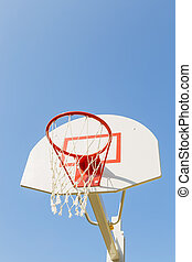 Game sports, competitions. Team sports, outdoor leisure, active recreation, entertainment. Basketball hoop with net on the backboard against the blue sky in the schoolyard outdoors