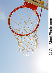 Game sports, competitions. Team sports, outdoor leisure, active recreation, entertainment. Basketball hoop with net against blue sky in a schoolyard outdoors