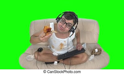 Gamer eating pizza and wipes his hands on himself