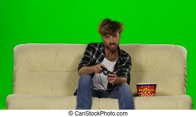 Gamer is playing with a joystick while eating popcorn. Green...