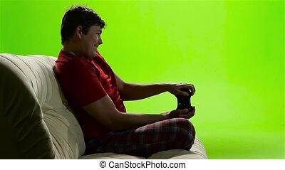 Gamer man intently playing a video game. Green screen studio