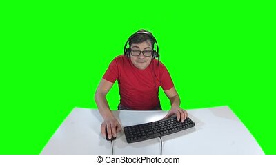 Gamer playing computer game sitting at the table. Green screen